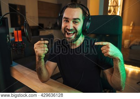 Happy young man gamer streamer in headphones playing on computer talking with players on chat in gaming competition celebrating win showing credit card