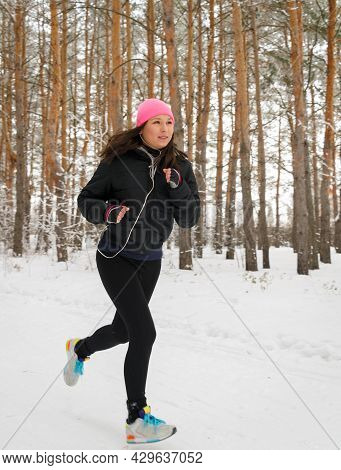 Running Woman. Female Runner Jogging In Cold Winter Forest Wearing Warm Sporty Running Clothing And