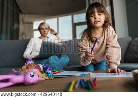 Young mother and her preschooler daughter in the living room, mother working on laptop computer