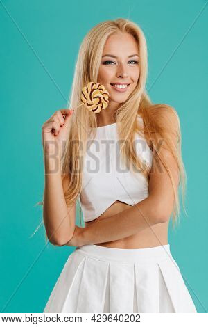 Happy smiling young blonde white woman standing over blue background holding lollipop