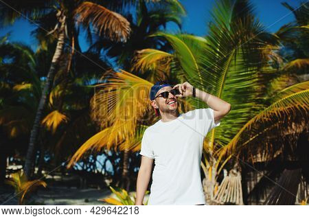 Cheerful Attractive Bearded Tourist Boy In White Tshirt Smiling Broadly While Adjusting Sunglasses A