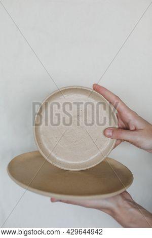 Hands Holding Ceramic Plates Isolated On White Background. Minimalist Set Of Handmade Ceramic Tablew
