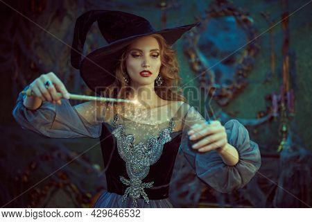 Magic Halloween. Enchanting young witch casts a spell with a magic wand in an old castle. Fairy tales.