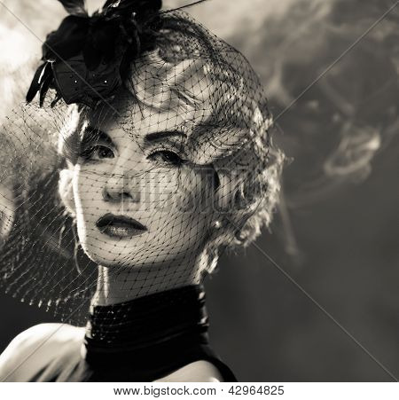 Elegant blond retro woman  with red lipstick wearing little hat with veil in smoke