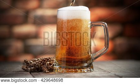 Pouring beer into pint, stylish brick wall on background. Fresh beverages and pub backgorund.