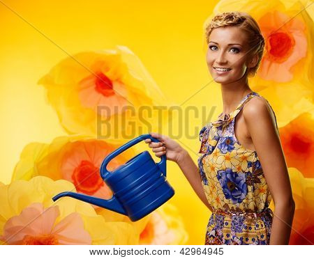 Beautiful young cheerful blond woman in colorful dress among big yellow flowers with watering can