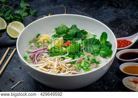 Soup Pho Bo With Beef, Lime And Spices On Black Stone Table With Sauces, Vietnamese Food