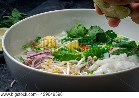 Soup Pho Bo With Beef, Lime And Spices On Black Stone Table With Sauces, Vietnamese Food, Close Up W
