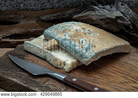 Mold Growing Rapidly On Moldy Bread Slices In Green And White Spores And Knife On Wooden Cutting Boa