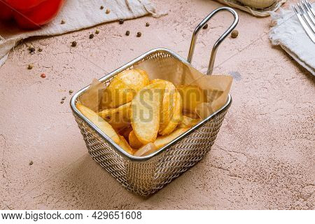 The Potatoes Wedges On The Board On Concrete Table