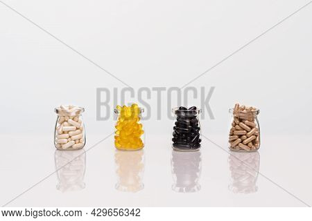 A Set Of Organic Vitamin And Supplement Capsules In Transparent Jars On A White Table With Reflectio