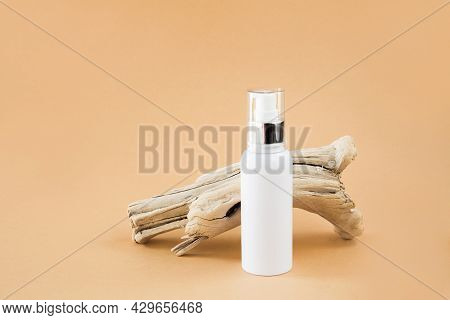 White Cosmetic Container With A Dispenser And A Dry Wooden Branch On A Beige Background. Concept Of