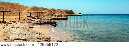 Sandy And Rocky Coast With Palm Beach Umbrellas. Desolate Resort Beach On The Coast Shore Of Red Sea