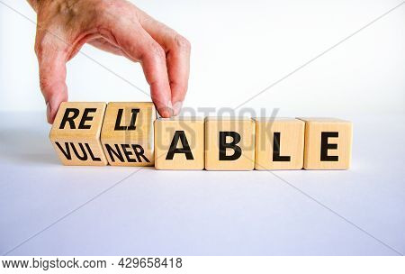 Vulnerable Or Reliable Symbol. Businessman Turns Wooden Cubes And Changes The Word Vulnerable To Rel