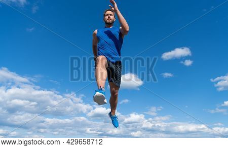 Muscular Man Sprinter Running In Sportswear Outdoor On Sky Background, Marathon
