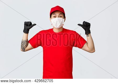 Cheerful, Happy Asian Delivery Guy In Red Cap And T-shirt, Wearing Protective Gloves And Medical Mas