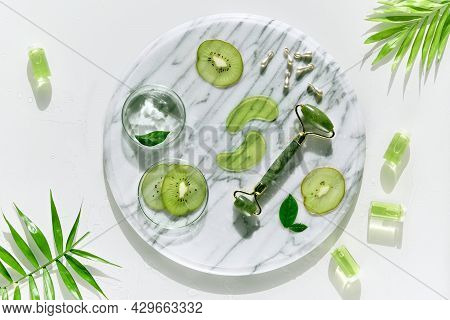 Cosmetic Skincare Background. Herbal Medicine With Kiwi Slices And Palm Leaves. Homemade Sugar Scrub