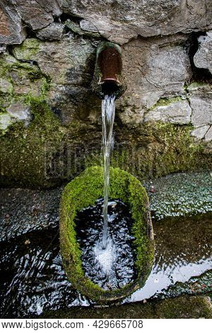 Water From A Forest Spring Flows Through A Metal Pipe Lined With Stones. Natural Source Of Clean Wat