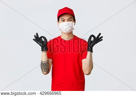 Stay Calm And Deliver Fast. Relaxed Smiling Asian Man In Red Cap And T-shirt, Wearing Protective Mas