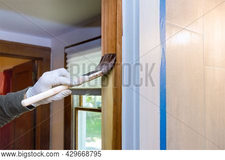 Hand Of Repairman Painting With Gloves In The Brush Applying Varnish Paint Wood Doors Molding Trim W