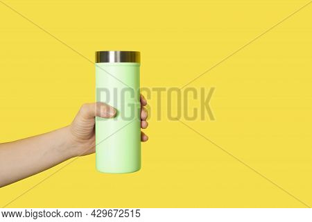 Hand Holds Light Yellow Travel Mug Isolated On White Background. Thermo Cup Or Tumbler In Female Han