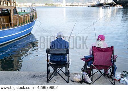 Turkey, Alanya - November 9, 2020: Elderly Couple Is Fishing In The Port Of Alanya. Pleasant Leisure