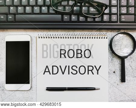 Phrase Robo Advisory Written On Notebook With Pen,smartphone,magnifying Glass,keyboard And Eye Glass