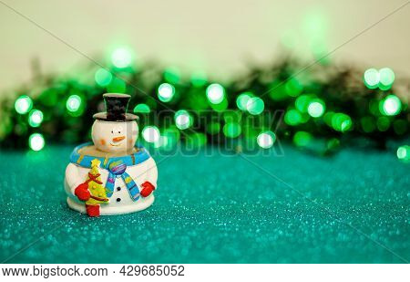 Funny Snowman. Winter Background. Festive Snowman With Christmas Lights Background. Merry Christmas