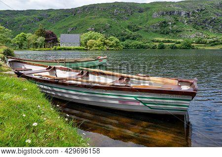 Ballingeary, Ireland- July 11, 2021: Row Boats On The Lake Near The Small Church At St Finbarr's Ora
