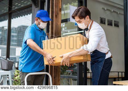 Asian Postman Deliver Food Ingredient Box To Restaurant Waiter In Cafe. Attractive Barista Worker We
