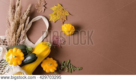 Autumn Harvest Of Squash And Squash In Eco Bag On Brown Background, Flat Lay, Copy Text