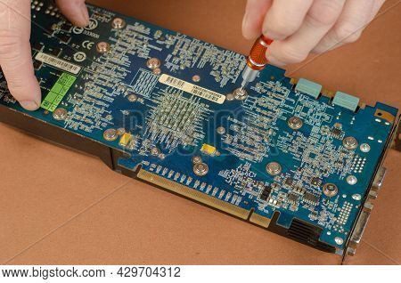 Graphics Card Brand Gigabyte Nvidia Geforce On A Brown Background. Man Disassembles Computer Compone