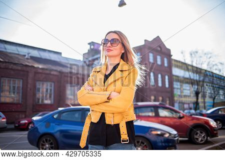 Attractive Woman In Sunglasses On The Background Of An Old Brick Building. A Woman In The City In A