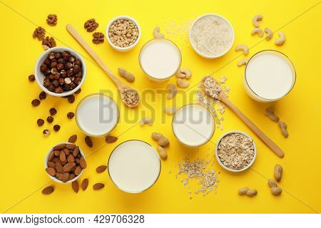 Different Vegan Milks And Ingredients On Yellow Background, Flat Lay