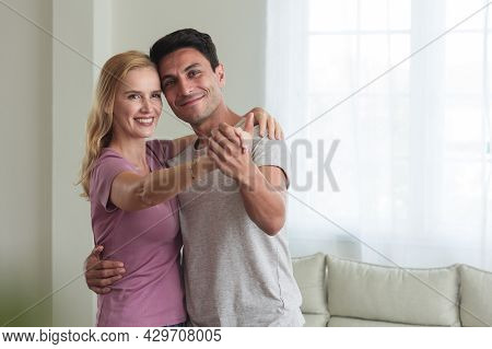 Romantic Caucasian Couple. Adult Woman And Man Are Enjoying Dancing In The Living Room. Wife And Hus
