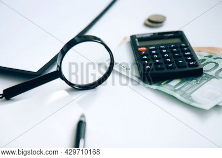 Calculator, Paper Money, A Stack Of Coins And A Folder With Documents Isolated On White Background.