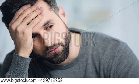 Dissatisfied And Bearded Man Touching Forehead And Looking Away.