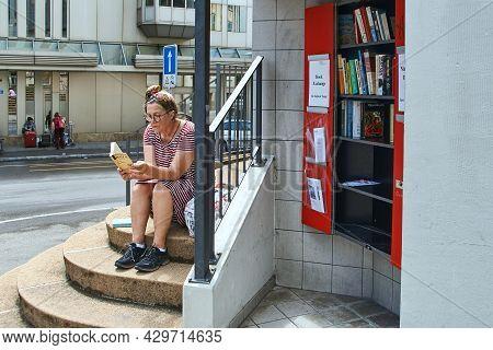 Zurich, Switzerland, July 10, 2017: Woman Reading A Novel By Honore De Balzac By A Street Book Excha