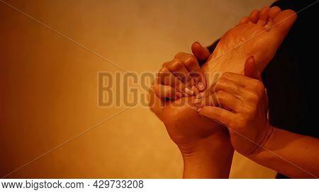 Cropped View Of Masseur Massaging Leg Of Barefoot Woman On Massage Table.