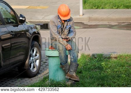 Worker In Safety Helmet And Dirty Uniform Sitting With Smartphone On A Street. Labour And Leisure, R