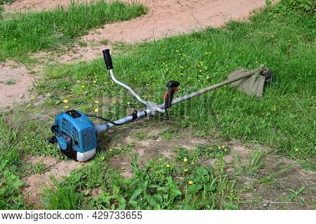 Trimmer Is Lying On Grass. Concept Of Garden Work. Lawn Care With Lawn Mower, Brush Mower Or Electri
