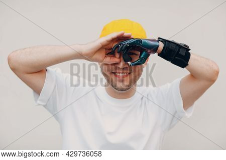 Young Disabled Man Looking Binoculars Gesture With Artificial Prosthetic Hand In Casual Clothes