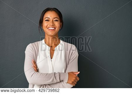 Beautiful mid adult african american woman standing on grey wall with crossed arms. Mature indian woman isolated on gray background. Portrait of smiling hispanic lady looking at camera.
