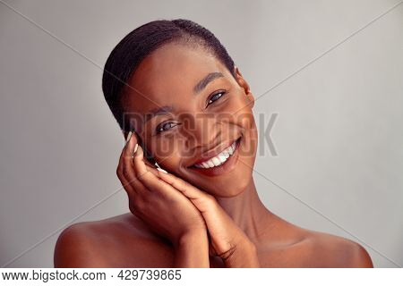 Portrait of mature african woman feeling fresh after spa treatment. Happy black mid adult woman with flawless skin smiling and looking at camera. Portrait of beauty lady isolated on grey background.