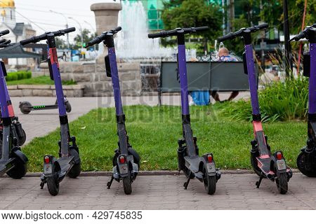 Electric Scooters In Row On The Parking Lot City Bike Rental System, Public Kick Scooters On The Str