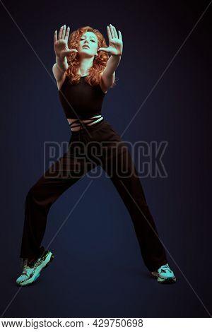 Modern dance. Full length portrait of a professional modern style dancer girl dancing at studio on a dark blue background.