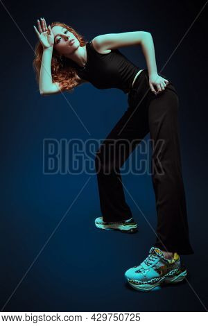 Full length portrait of a professional modern style dancer girl dancing at studio on a dark blue background. Contemporary dance.