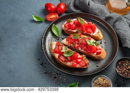 Three Bruschetta With Tomatoes, Basil And Cheese On A Black Plate. A Traditional Italian Snack. Side