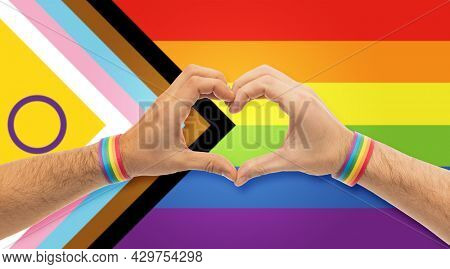 lgbtq, trans and intersex rights concept - close up of male couple hands with rainbow wristbands showing heart gesture over progress pride flag on background
