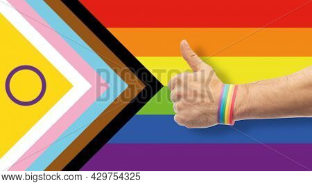 lgbtq, trans and intersex rights concept - close up of male hand wearing rainbow wristband showing thumbs up over progress pride flag on background